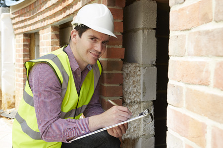 insulating: Architect Checking Insulation During House Construction Stock Photo