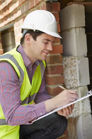 architect: Architect Checking Insulation During House Construction Stock Photo