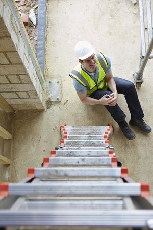 건설 노동자는 사다리에서 떨어지는 그리고 다리 부상