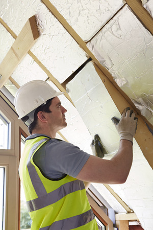 home builder: Builder Fitting Insulation Boards Into Roof Of New Home
