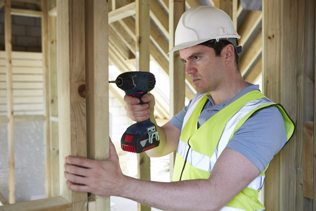 cordless: Construction Worker Using Cordless Drill On House Build Stock Photo