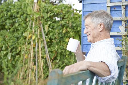 hombre tomando cafe: Hombre mayor que se relaja en jard�n con la taza de caf� Foto de archivo