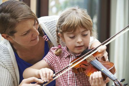 school teacher: Teacher Helping Young Female Pupil In Violin Lesson