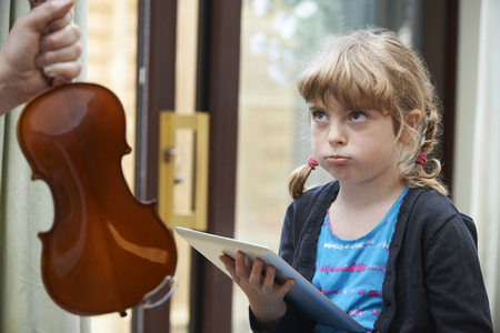 teaching music: Young Girl Would Rather Play On Digital Tablet Than Practise Violin Stock Photo