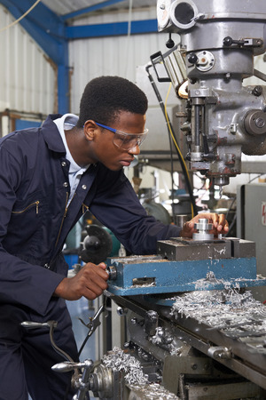 boy 18 year old: Male Apprentice Engineer Working On Drill In Factory Stock Photo