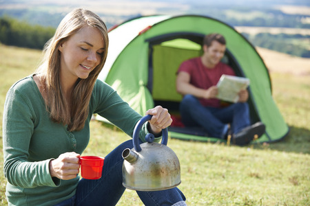 whilst: Couple Making Hot Drink Whilst Camping In Countryside