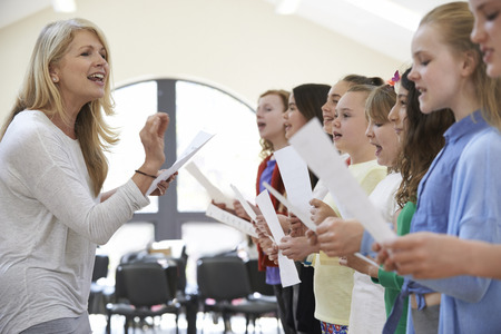 encouraged: Children In Singing Group Being Encouraged By Teacher