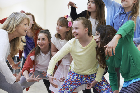 lesson: Group Of Children With Teacher Enjoying Drama Class Together Stock Photo