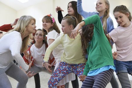 Group Of Children With Teacher Enjoying Drama Class Together Stock Photo