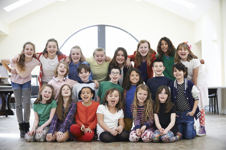 Large Group Of Children Enjoying Drama Workshop Together