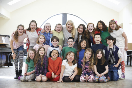 Large Group Of Children With Teacher Enjoying Drama Workshop Together