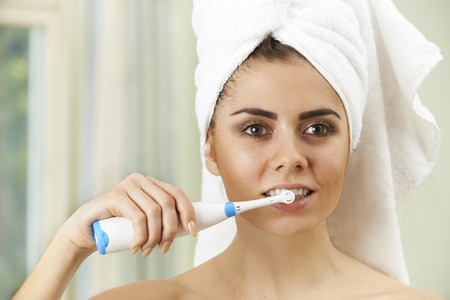 Woman Brushing Teeth With Electric Toothbrush In Bathroom Фото со стока