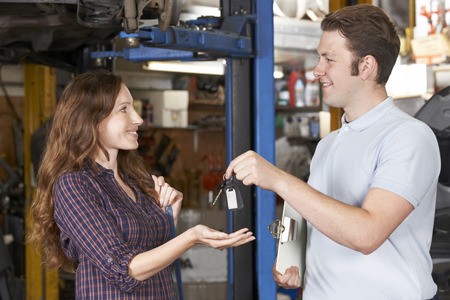 auto repair shop: Satisfied Customer Collecting Car From Garage Mechanic