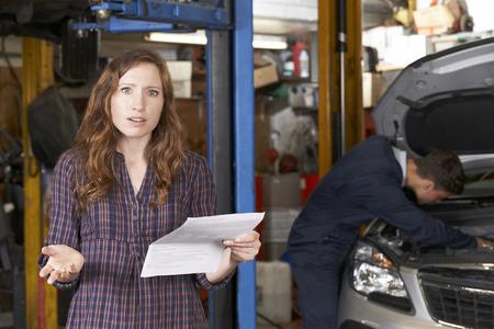 factura: Mujer sorprendida al cliente Mirando a Bill Garaje Foto de archivo