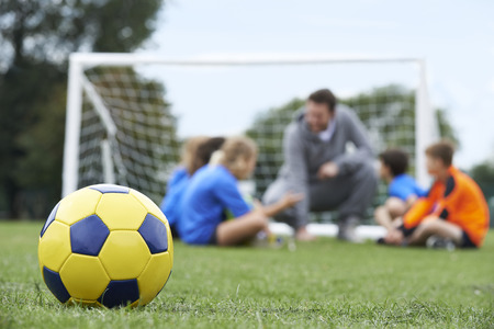 sports: Coach  And Team Discussing Soccer Tactics With Ball In Foreground Stock Photo