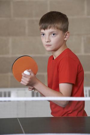 school gym: Boy Playing Table Tennis In School Gym