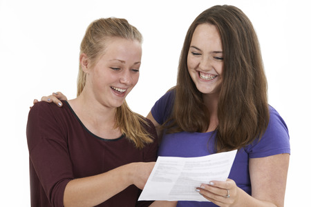 exam results: Studio Shot Of Two Female Teenage Friends Celebrating Exam Result