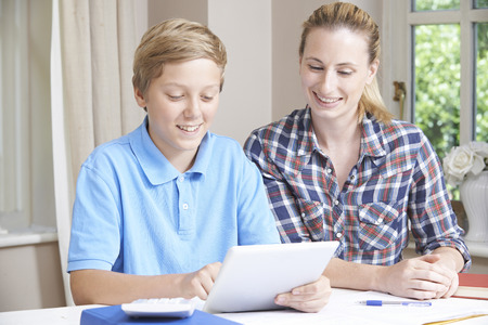 Female Home Tutor Helping Boy With Studies Using Digital Tablet Stock Photo