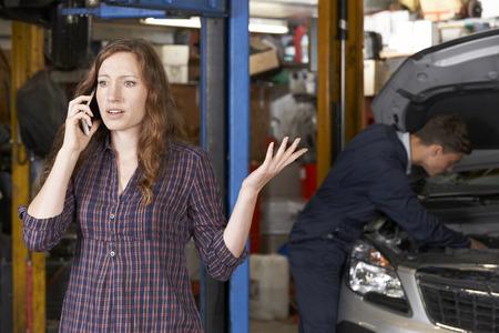 Frustrovaný Žena zákazníků na mobilní telefon opravně auto