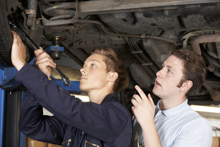motor vehicle: Mechanic And Apprentice Working On Car Together