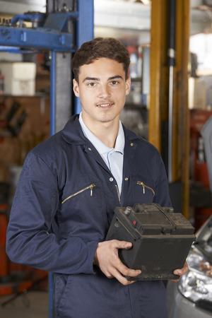 auto repair: Apprentice Mechanic Holding Car Battery In Auto Repair Shop