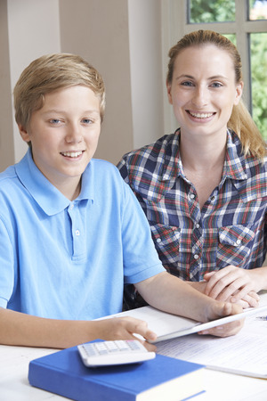 school year: Female Home Tutor Helping Boy With Studies Using Digital Tablet Stock Photo