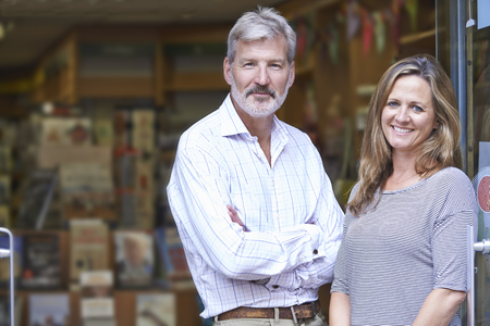 retail: Portrait Of Couple Who Own Bookshop Outside Store