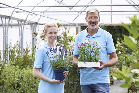 small business team: Portrait Of Staff At Garden Center Holding Plants