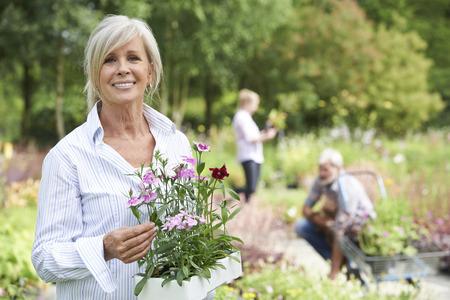 femmes souriantes: Femme d'âge mûr Choisir des plantes au Garden Center
