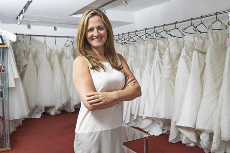 small business owner: Portrait Of Female Bridal Store Owner With Wedding Dresses
