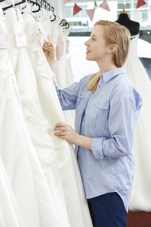 price tag: Bride Looking At Price Tag On Wedding Dress In Bridal Boutique