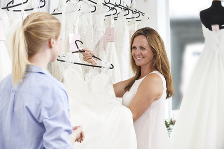 sales assistant: Sales Assistant In Bridal Store Helping Bride To Choose Wedding Dress Stock Photo