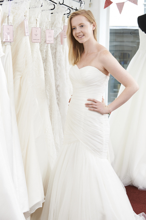 trying: Bride Trying On Wedding Dress In Bridal Boutique Stock Photo