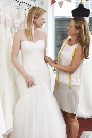 wedding dress: Bride Being Fitted For Wedding Dress By Store Owner Stock Photo