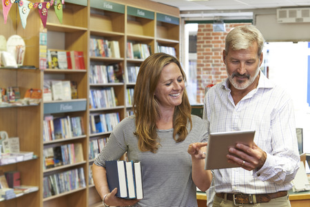 Male And Female Owners Of Bookstore Using Digital Tablet Stockfoto