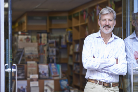 shop interior: Portrait Of Male Bookshop Owner Outside Store