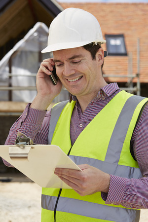 high visibility: Architect On Building Site Using Mobile Phone Stock Photo