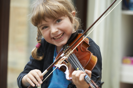 violins: Portrait Of Young Girl Learning To Play Violin