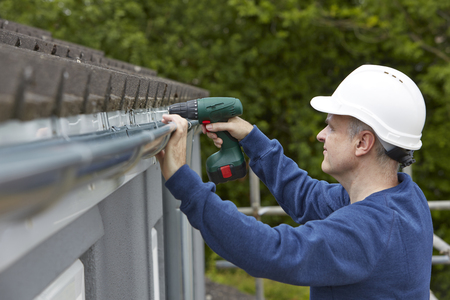 gutter: Workman Replacing Guttering On Exterior Of House