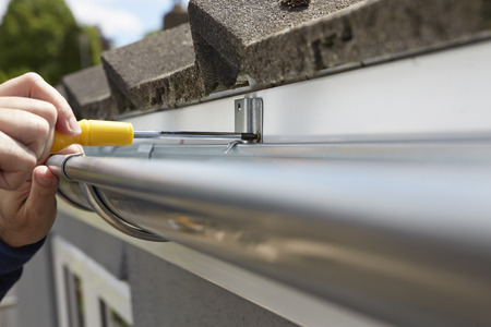 gutter: Close Up Of Man Replacing Guttering On Exterior Of House