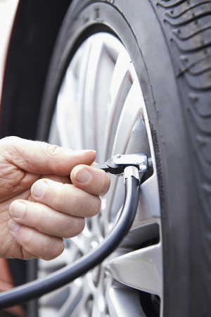 car maintenance: Close Up Of Man Inflating Car Tyre With Air Pressure Line