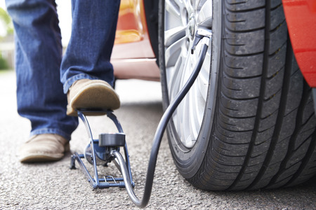 flat tyre: Close Up Of Man Inflating Car Tyre With Foot Pump Stock Photo