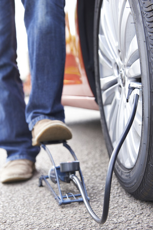pumping: Close Up Of Man Inflating Car Tyre With Foot Pump Stock Photo