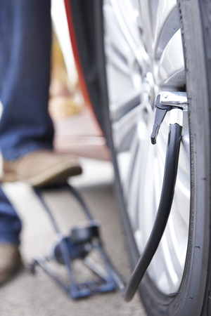 inflating: Close Up Of Man Inflating Car Tyre With Foot Pump Stock Photo