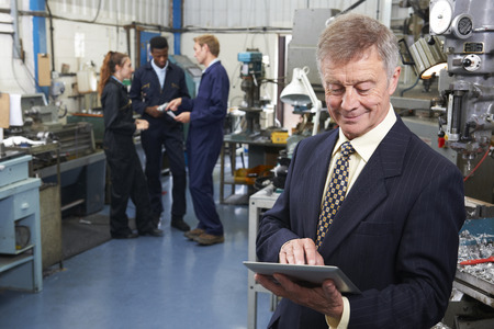 small business team: Owner Of Engineering Factory Using Digital Tablet With Staff In Background Stock Photo