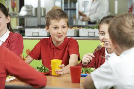 Grupa uczniów siedzi w szkole Cafeteria jeść posiłek