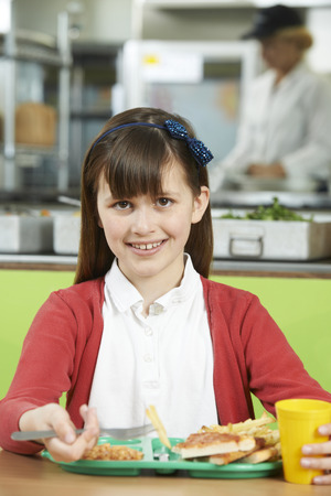 school cafeteria: Female Pupil Sitting At Table In School Cafeteria Eating Unhealthy Lunch