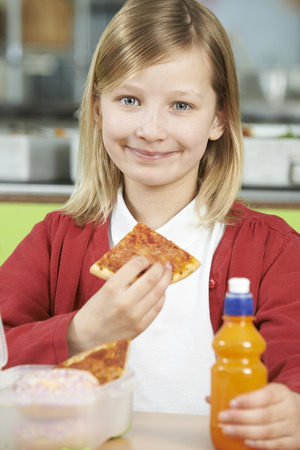 school cafeteria: Girl Sitting At Table In School Cafeteria Eating Unhealthy Packed Lunch