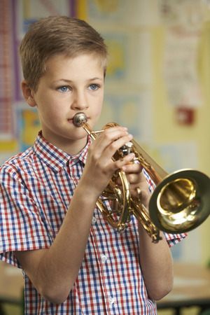 musical instrument: Boy Learning To Play Trumpet In School Music Lesson