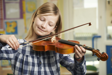 school band: Girl Learning To Play Violin In School Music Lesson